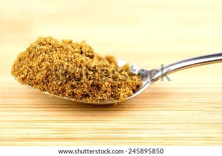 Macro closeup of crushed cumin seeds in spoonful - stock photo