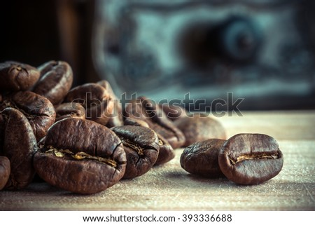 Macro closeup photo of roasted coffee beans laying on the wooden table. Natural coffee beans. Black coffee seeds. Brown aroma composition of coffee beans flavor. - stock photo