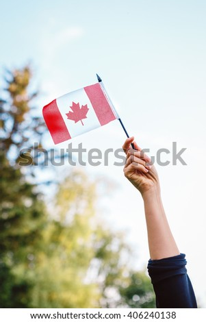 Macro closeup shot of hand arm waving a red white canadian flag with maple leaf on blue sky and green forest nature background outside  - stock photo