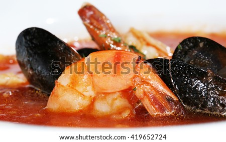 macro delicious red soup with mussels in a white plate on a dark background - stock photo