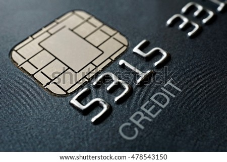 Macro detail of a brand new black and gray luxurious credit card with focus on the caption Credit, metal electronic chip and embossed numbers and letters as a symbol of credit and getting into debts