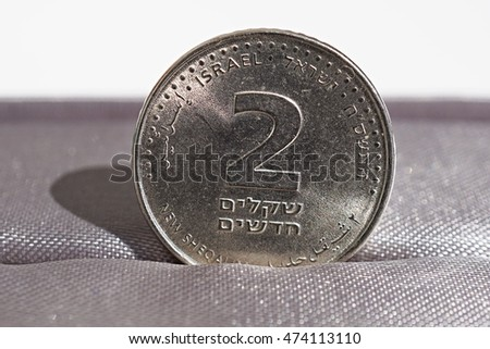 Macro detail of a silver coin of two Shekels (Israeli currency New Shekel, ILS) placed in the gift box as a symbol of luxury and highly appreciated currency of Israel
