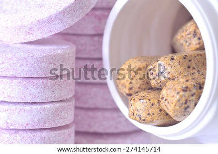 Macro detail of bottle of multivitamin supplement pills and soluble purple magnesium tablets in foreground - stock photo