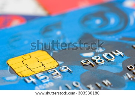Macro detail of the numbers on a plastic credit card with golden electronic chip - stock photo