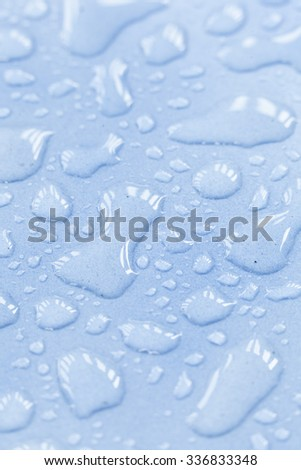 Macro drops of water droplets perched on tile floor blue. - stock photo