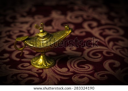 Macro image of a tiny, gold antique Aladdin lamp ornament close-up. - stock photo
