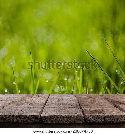 macro image of green grass background with waterdrops hanging on the leaves being backlit by the sun in the morning with wooden plank floor - stock photo