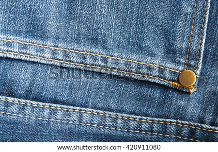 Macro image of old brass button of blue jeans texture - stock photo