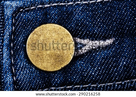 Macro image of old grungy brass button of blue jeans texture - stock photo