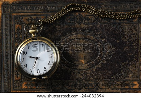 macro image of old vintage pocket watch on antique book. top view. retro filtered image  - stock photo