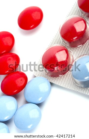 macro image of red and blue pills on white background