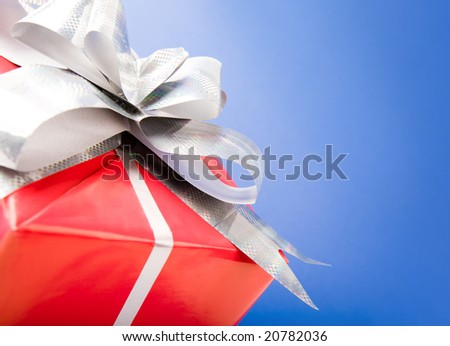 Macro image of silver knot on red giftbox isolated over blue background - stock photo