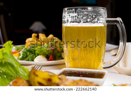Macro Mug of Cold Beer on Dining Table Surrounded by Assorted Main Dishes - stock photo
