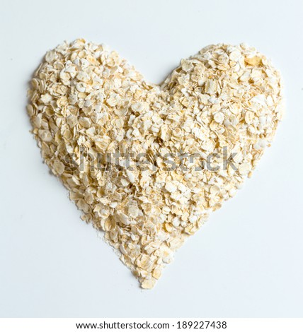 Macro Oat flakes pile heart  on the white background - stock photo
