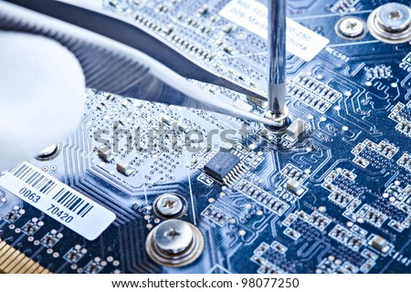macro of a hand holding tweezers on a laptop screw - stock photo