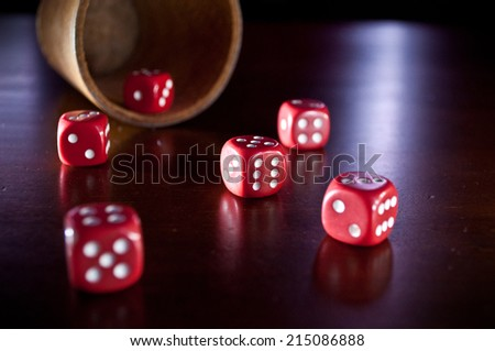 Macro Of A Lying Leather Dice Cup And Collection Of Six Dices On A Wooden Table At Night