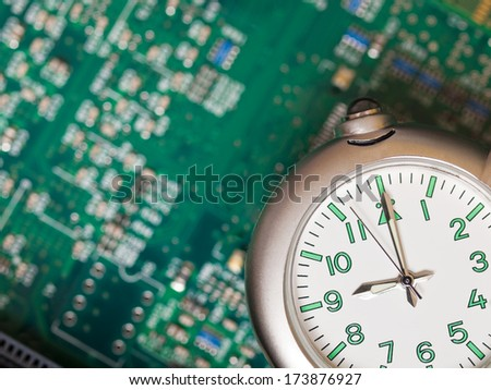 Macro of a watch with a blurred background of a computer motherboard