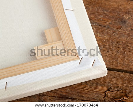 Macro of an artist canvas on wooden table - stock photo