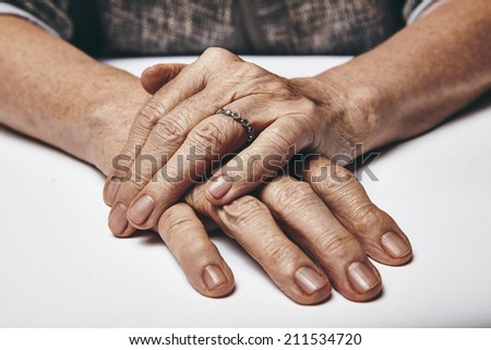 Macro of an old lady sitting with her hands clasped on a table. Elderly woman's hands with a ring resting on grey surface. Focus on hands. - stock photo