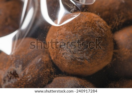 Macro of appetizing sphere of chocolate truffles in plastic bag. Chocolate powder. Shooting in studio. - stock photo