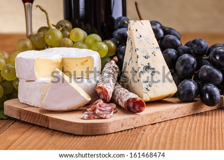 Macro of Camembert, blue cheese and dry sausage snack with grape cluster