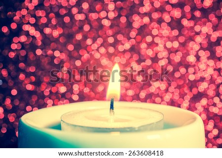 Macro of candle with fire against defocused lights - stock photo