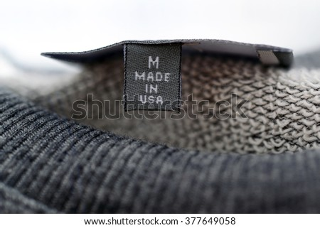 """macro of clothing label whit text: """"made in USA"""". brown sweater on white background. - stock photo"""