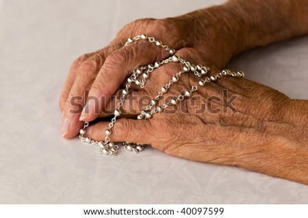 macro of elderly caucasian hands holding a silver rosary - stock photo
