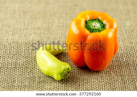 Macro of flavorful orange capsicum and curved yellow wax pepper - stock photo