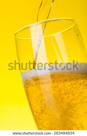 Macro of fresh beer being pured into glass on yellow background - stock photo