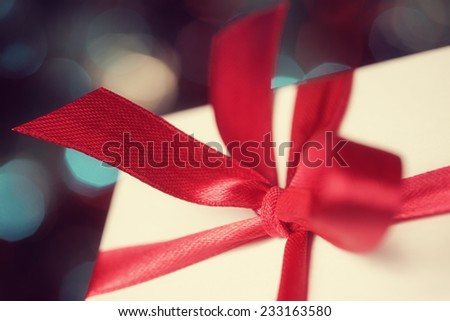 Macro of gift box with red bow against defocused lights - stock photo