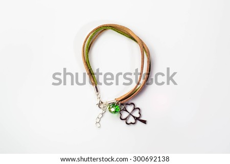 Macro of handmade bracelet made with colorful leather straps, clover pendant and crystal glass isolated on white background, top view.