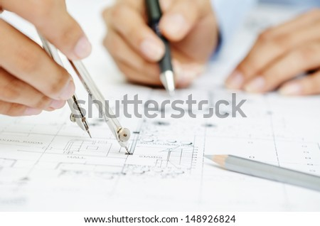 Macro of hands on blueprint - stock photo