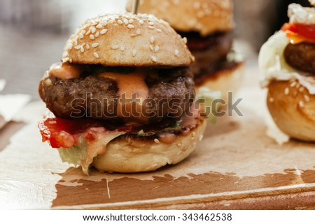 Macro Of Mini Burgers Sliders On Rustic Wooden Plate - stock photo