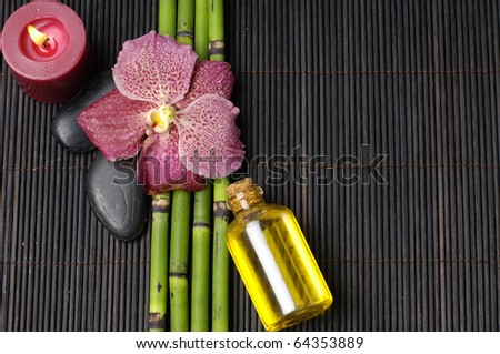 Macro of orchid and parfume bottle and candle on mat - stock photo