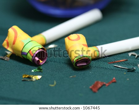 Macro of party blowers on a teal tablecloth - stock photo