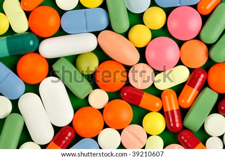 Macro of pills and capsules on green background