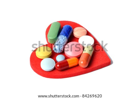 Macro of pills and capsules on red heart
