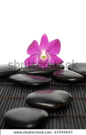 Macro of pink orchid with pebble on bamboo stick straw mat - stock photo