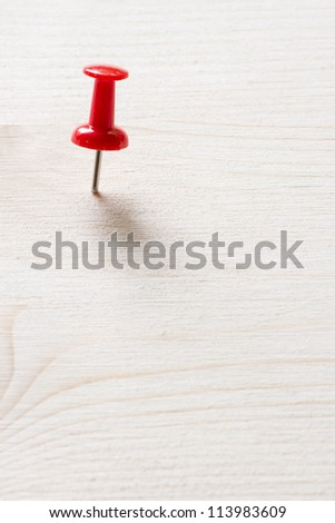 Macro of red push pin on the wood plane