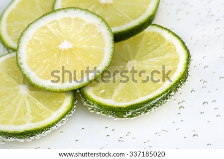 macro of several green lime slices - stock photo