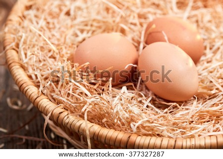 Macro of three raw eggs in an easter nest with straw in a basket.