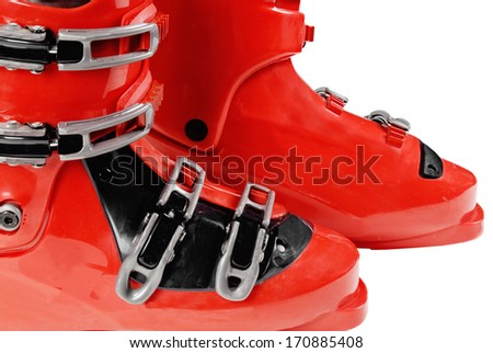 Macro of two red snow ski boots trimmed with black and several buckles on an isolated white background. Rubber boots provide safety to the skier and stability. - stock photo