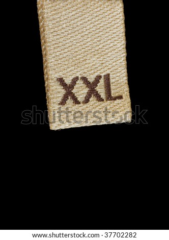 Macro of XXL size clothing label, isolated on black - stock photo