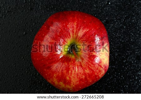 macro one red apple with drops of dew on a black background studio - stock photo