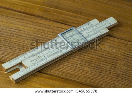 Macro photo, close-up range high-precision hand-held calculating tools - logarithmic ruler  brown wooden background