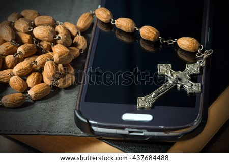 Macro photo of a metal crucifix with wooden rosary beads on a used smartphone and Holy Bible - stock photo