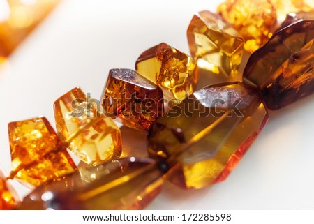 Macro photo of amber beads on white background. Selective focus - stock photo