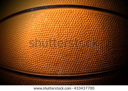 Macro photo of an old black and orange basketball with dark shadows - stock photo