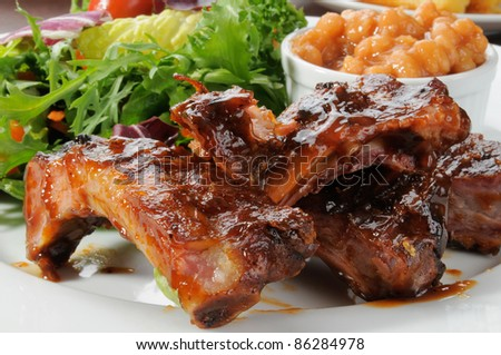Macro photo of baby back ribs drenched in barbecue sauce with baked beans and greens - stock photo